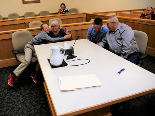 Ryan Levin, left, hugs Jan Levin and Charles Levin talks to David Levin after District Judge Sandra Price finalized their adoption on Nov. 14 in Farmington District Court.