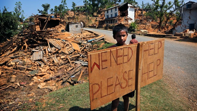A Nepalese boy stands outside his village with a signboard asking for help in Pauwathok village, Sindhupalchok district, Nepal, on May 2.
