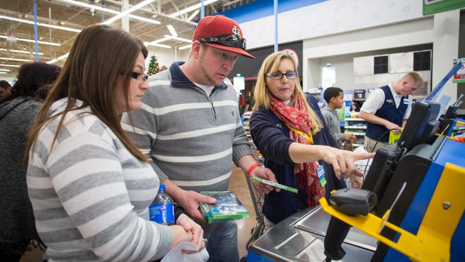 Chris and Mary Finley check out during Walmart's Black Friday shopping event on Thursday, Nov. 26, 2015 in Rogers, Ark. Walmart announced Thursday that it will start rolling out a mobile payment method in stores similar to Apple Pay.