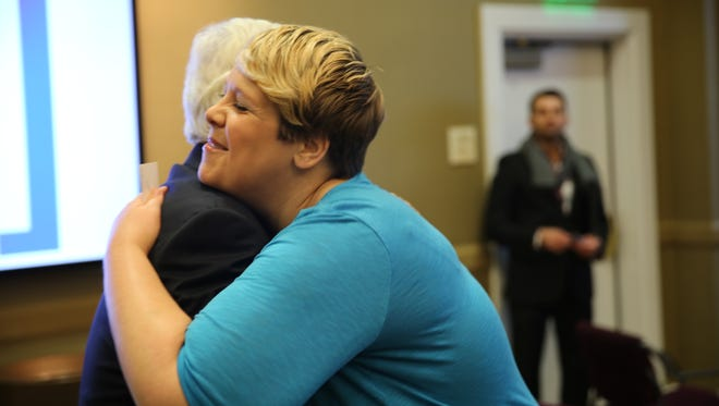 Rebecca Collett, a felon, hugs Jefferson County Attorney Mike O'Connell. The pair were at a news conference calling for expungement reform.