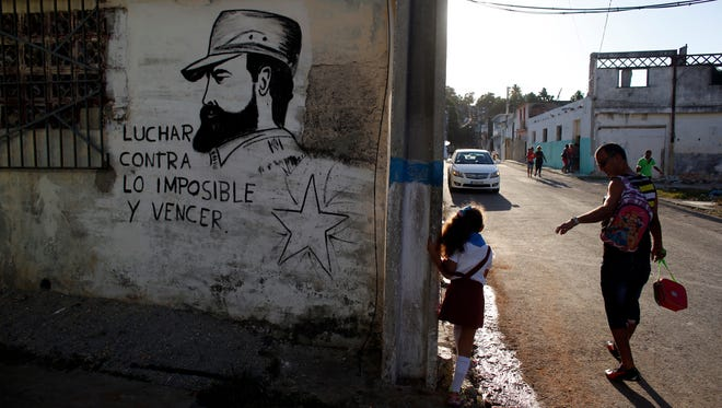 """A man walks his daughter back from school past a wall with a mural of the late Fidel Castro, flanked by a quote from Castro that says in Spanish: """"Fight against the impossible and overcome"""" in Havana, Cuba, on Monday."""