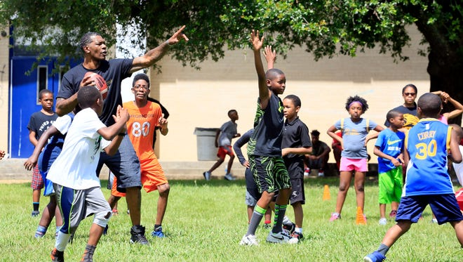 Mentor and coach John Knight throws a pass while leading children in a game of touch football during the J.T. and Friends Youth Sports Camp at Callaway High School Tuesday.