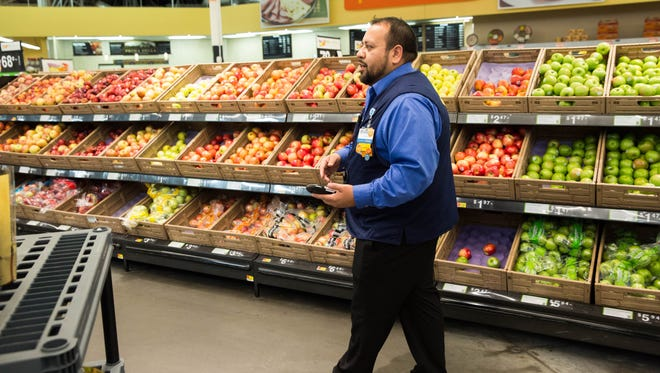Ray Clark, assistant manager for Online Grocery Pickup at the Walmart on Rinconada Boulevard, explains the the way personal shoppers select the items on customers' shopping lists before bagging and getting them ready for pickup on Thursday October 19, 2017.