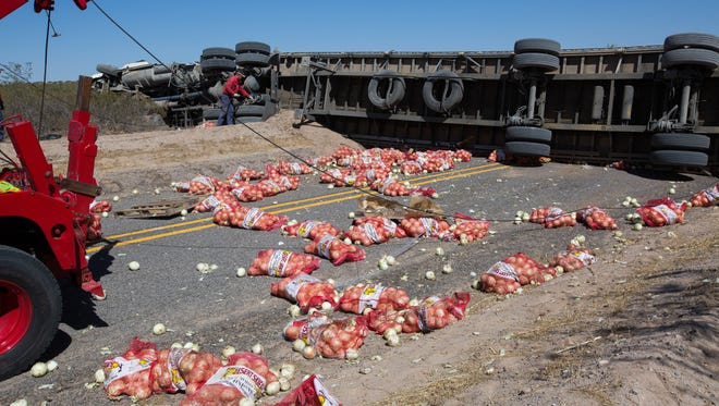 Crews from Kleine Towing along with New Mexico Department of Transportation and New Mexico State Police work to clean up an accident where a semi-truck carrying onions flipped on Las Alturas near Vado, Monday June 11, 2018.