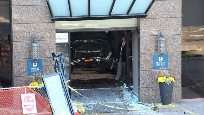 Then-firefighter Erik Refvik's car is shown in the lobby of the Halstead White Plains apartment house where it landed after a fatal crash on S. Lexington Avenue in White Plains in 2014. A fellow firefighter, Brian Noonan, now faces disciplinary charges over the handling of evidence from the vehicle.