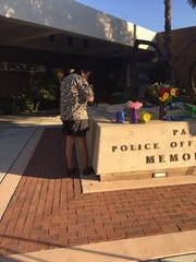 Al Contreras lays candles on a memorial outside the