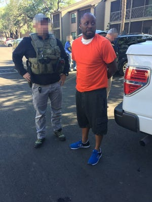 U.S. Marshals Task Force agents arrest Leavy L. Johnson at an apartment complex in Tampa, Fla., on Friday, April 7, 2017. Johnson was indicted in January in the rape of a woman at Bridgestone Arena in Nashville. Nashville police blurred the faces of the agents in the photograph to protect their identities in undercover work.