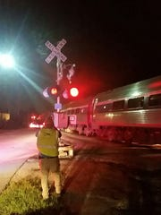 A CSX investigator takes a photo of one of the function crossing signals on Thornton Ave. in Dayton, Kentucky where a motorist was struck Monday morning.