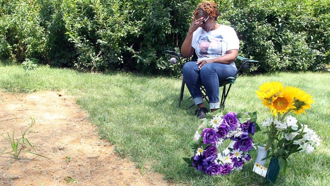 Tressa Sherrod, whose son, John Crawford III, 22, was shot and killed by a Beavercreek police officer while holding an an air rifle/pellet gun he picked up from a store shelf  in a Beavercreek Wal-Mart store, visits her son's grave in Spring Grove Cemetery on the one-year anniversary of his death. Sherrod lives in Colerain Township. She sits at the grave at least once a week, sometimes accompanied by her mother, Annie Trimm, of Bond Hill.