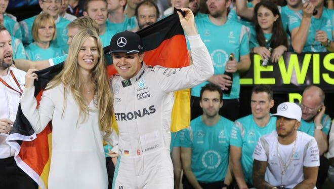 Nico Rosberg is sprayed with champagne by his team after winning the Formula One title.