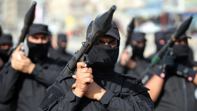 Iraqi Shiite fighters parade with their weapons on June 21 in the capital, Baghdad.