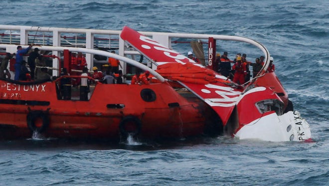 Indonesian search and rescue personnel pull wreckage of AirAsia flight QZ8501 onto the Crest Onyx ship at sea.