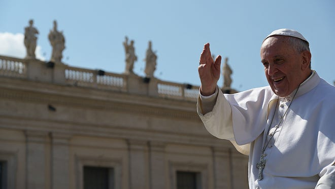 Pope Francis waves to people on March 18 as he leaves St. Peter's Square at the Vatican after his weekly general audience.