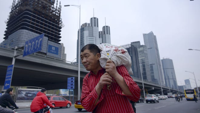 A man carries a package as he walks along a street at a Central Business District in Beijing on April 1, 2015.