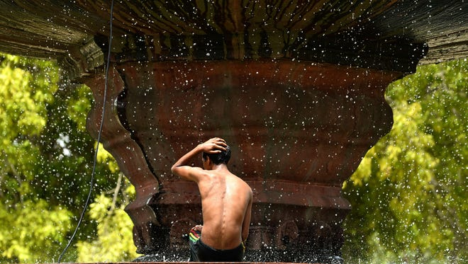 An Indian boy takes a bath at a fountain at India Gate in New Delhi on May 26, 2015.