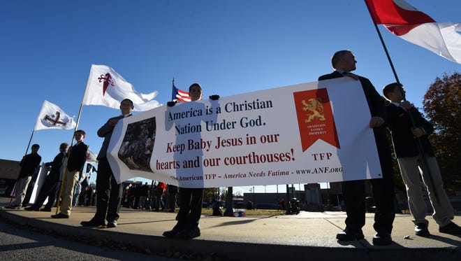 A group of protesters hold up a sign Sunday demanding the baby Jesus be brought back to the Baxter County Courthouse following a lawsuit. Whether the nativity scene will appear on the courthouse lawn, along with other displays of faith, will depend on the decision of elected county officials.