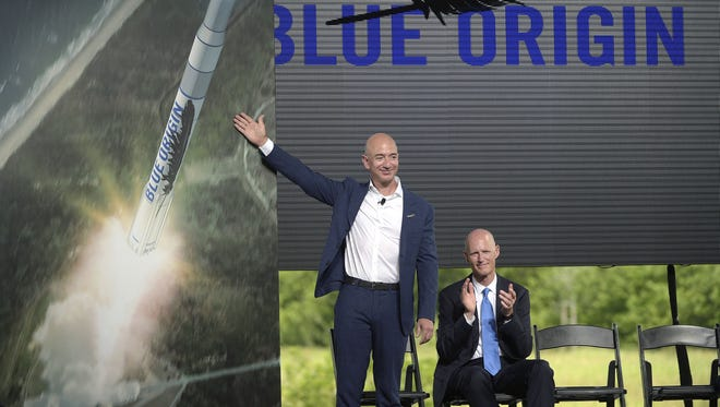 Amazon CEO Jeff Bezos, left, unveils the new Blue Origin rocket, as Florida Gov. Rick Scott applauds, during a news conference at the Cape Canaveral Air Force Station in Cape Canaveral, Fla., in September