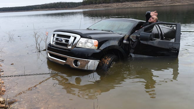 Mountain Home diver Paul Worman signals for a tow truck operator to stop as they work to pull a Ford F150 from Bull Shoals Lake Monday morning. Drung Friday's storm, the driver accidentally put the truck in neutral while attempting to free another truck stuck in the mud at Howard Creek. The U.S. Army Corps of Engineers is warning area residents to be cautious around local waterways due to the heavy rains.