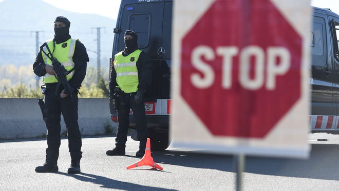 Catalan Autonomous Police officers, known as Mosso d'Esquadra, stand guard Nov. 14 at a toll station during vehicles controls on a motorway of Barcelona, a day after the terrorist attacks in Paris.