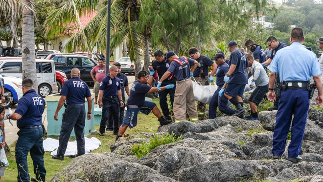 Emergency responders carry the body of a middle-aged man found floating along the rocky shoreline near the Paseo stadium in Hagatna on Wednesday, Dec. 2.