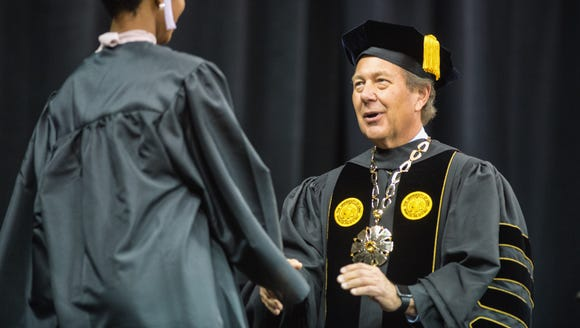 President Bruce Harreld congratulates a graduate during