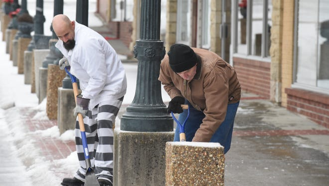 Baxter County jail inmate Christopher Gragg, left, shovels snow alongside Baxter County Building Superintendent John Harding Wednesday morning. A third storm bringing a mixed bag of precipitation is expected to move through the Twin Lakes Area this evening and overnight.