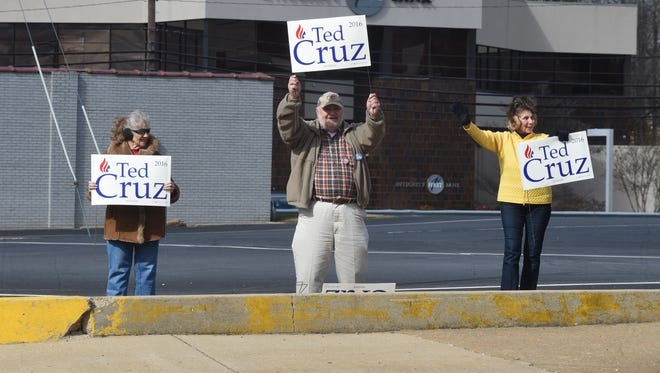 Ted Cruz supporters and Mountain Home residents Katherine Grace, left, Paul Schwindt, center, and Joyce Wagner hold up signs for Cruz across the street from the Baxter County Courthouse on Tuesday, the first day of early voting. Early voting  continues through Feb. 29.