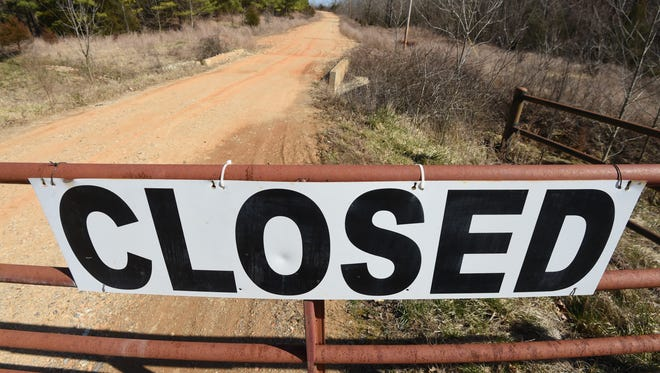 The road leading to the former NABORS landfill is barred by a triple-locked gate. A legal hearing in one of the half-dozen lawsuits filed against the Ozark Mountain Solid Waste District over the collection of a a yearly $18 service fee to repay its bondholders is scheduled for later this month in Berryville.
