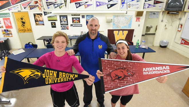 Students Tanner Horn, left, and Lexi Coroch, right, hold up pennants for the colleges they're interested in. Their Mountain Home High School teacher Jim Tejcek, center, has pennants for many colleges in his classroom to help spark discussions about students' college plans.
