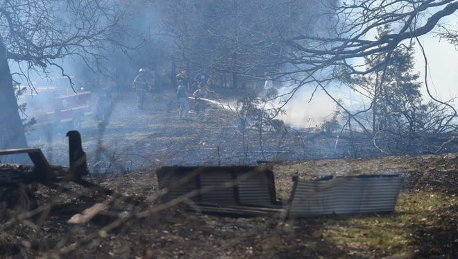 Firefighters work to extinguish a controlled burn that went out of control in rural Mountain Home Tuesday afternoon in the 200 block of County Road 454. High winds pushed fires across the Twin lakes Area Tuesday.