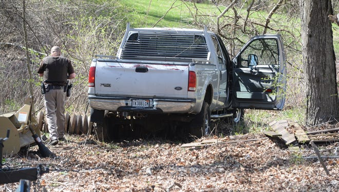 Wayne County Sheriff's Department officers Tuesday afternoon investigate a truck that was stolen and driven in a police pursuit before being crashed on Leeds Road south of Richmond.