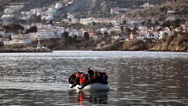 Migrants and refugees on a rubber boat arrive at the northern island of Lesbos after crossing the Aegean Sea from Turkey on Feb. 23, 2016.