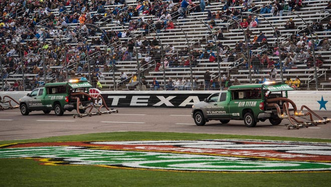Air titan trucks dry the track Saturday night before the Duck Commander 500 at Texas Motor Speedway.