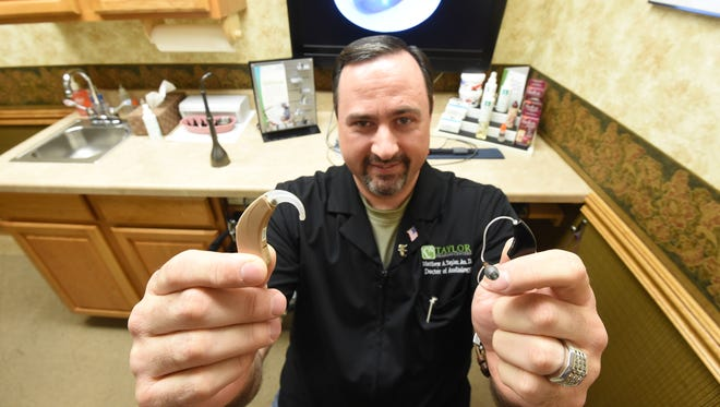 Dr. Matt Taylor holds up an older, clunky hearing aid to show the difference of the newer, far less visible hearing aids like the one in his right hand. Taylor has three suggestions for protecting your hearing and elaborates on them in the accompanying article.