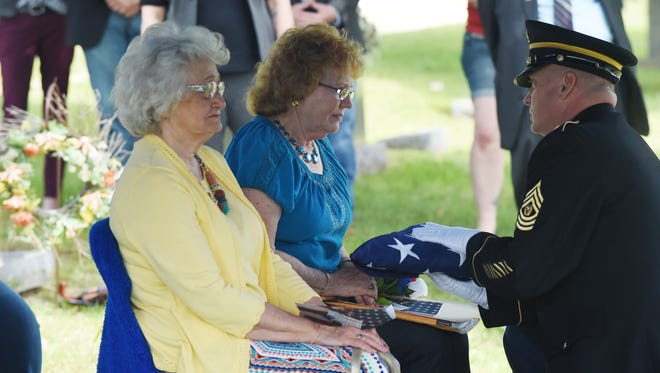 Pauline Mears, center, receives a flag Tuesday during a graveside service to honor the sacrifices of her brother, Yellville resident and Medal of Honor recipient Charles Leon Gilliland.