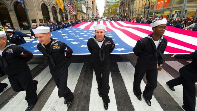 Sailors help carry the flag during the 2015 Veterans Day Parade in New York City.