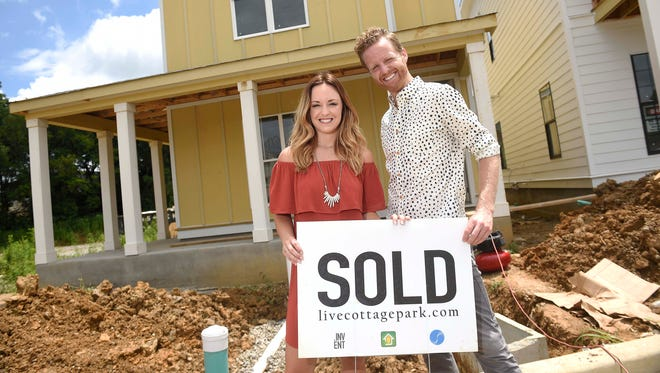 First-time home buyer Lindsay Alderson poses in front of her new home in the Cottage Park development in East Nashville with her Realtor, Robby Stone of Village Real Estate