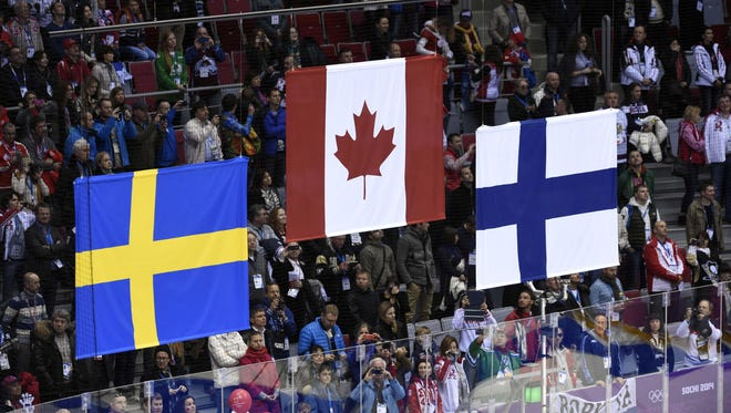 The flags for Sweden, Canada and Finland are raised during the medal ceremony after the men's hockey gold medal game in 2014 in Russia.