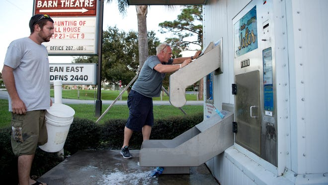 "Dennis Menesick (center), of Sewell's Point, and Mike Neal, of Stuart, wait for an ice machine to replenish itself Wednesday, Oct. 5, 2016, on Southeast Ocean Boulevard near Monterey Road in Stuart. ""Today's a lot better than yesterday,"" Menesick said, referring to the number of people out preparing for Hurricane Matthew. ""Although (today) I came up U.S. 1 from West Palm Beach, and no one had ice,"" he added."