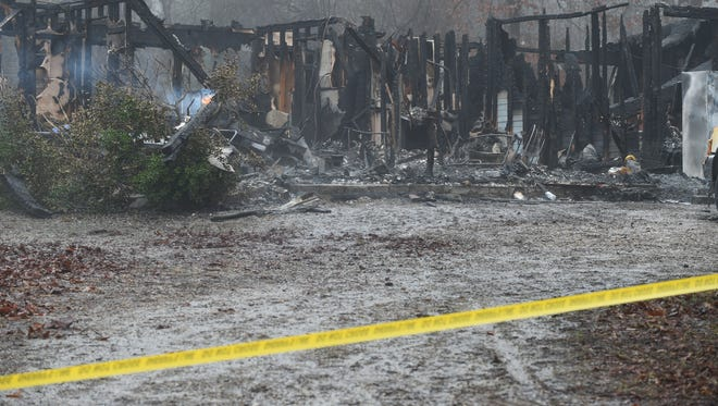A small fire burns at 78 Baxter County Road home of Mountain Home residence of 56-year-old Donna Lou Rollins whose body was found in the rubble of the Sunday night blaze. The fire remains under investigation.