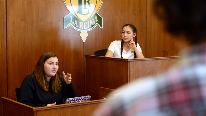 La Reina mock trial team member Kiva Runnels, left, at the witness box, practices with Talia Berriz and Alia Biswas, at the judge's bench, before the state competition in 2017.