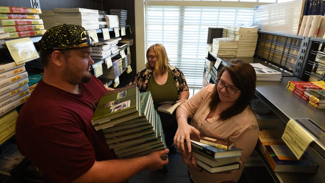 Phlebotomy student Wesley Nance (left), assistant store manager Tia Mitchell (middle) and nursing student Bethany White set up shelves for the fall summer semester. Arkansas State University-Mountain Home is participating in ArkansasGives on April 6, a one-day campaign where people donate to nonprofits.