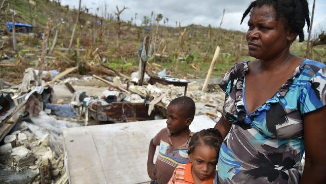 A mother and her children stand on the site of their destroyed home amid destruction from Hurricane Matthew in the area of Chabet, commune of Roche-a-Bateaux, in southwestern Haiti, on October 18, 2016.