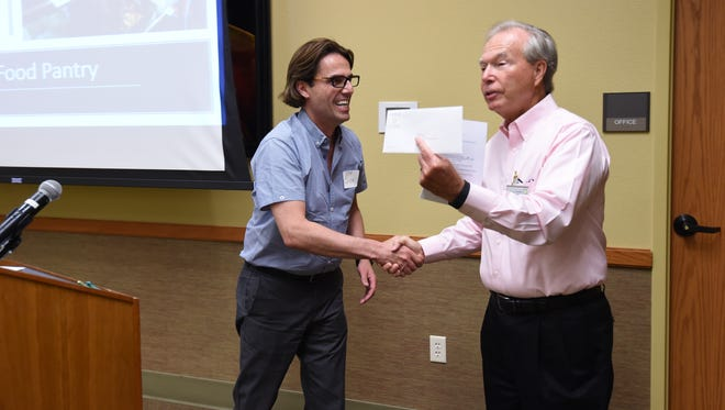 Jeff Quick, CEO and president of Food Bank of North Central Arkansas, (from left) accepts a check from Twin Lakes Community Foundation board member Elton Kirby during a grant ceremony Thursday at the Donald W. Reynolds Library. Several area nonprofits received grants.