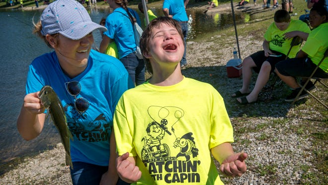 "Trevor Hill, 19, a student at Bosse High School, right, celebrates the kissing of his largemouth bass held by peer tutor Avery Ott, 17, during the ""Catchin' with Capin"" event at Eagle Lake in Evansville Monday morning. Although the smooch surprised Ott, some of the old-timers at the 10th annual event said it was a tradition to kiss your first fish of the day."