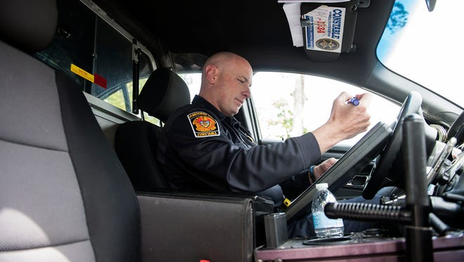 Constable Daniel Hollenbaugh sorts through some paperwork in his car, Wednesday, May 10, 2017. Hollenbaugh has been a constable since 2010.