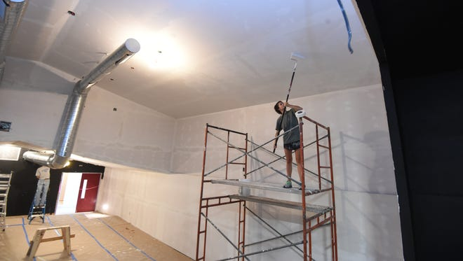 Marcella Schlote paints the ceiling of the Twin Lakes Playhouse Friday morning. The community theater is having a major facelift.