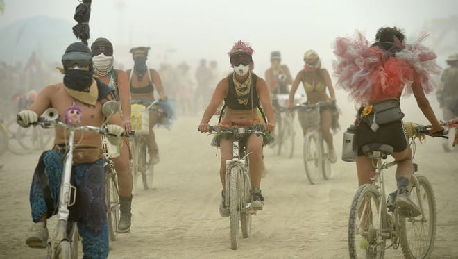 Burners ride through the streets of Black Rock City during a dust storm at Burning Man on August 28, 2017.