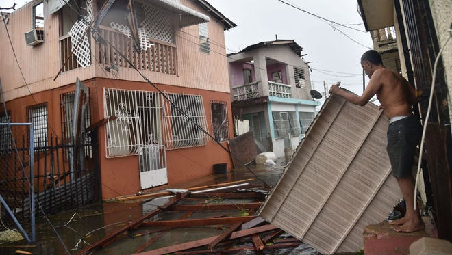 Residents of San Juan, Puerto Rico, deal with damage to their homes on Sept. 20, 2017, after Hurricane Maria battered the island.
