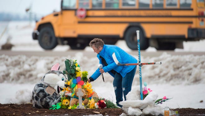 A woman lays flowers at a makeshift memorial set up at the intersection of Friday's fatal bus crash near Tisdale, Saskatchewan.